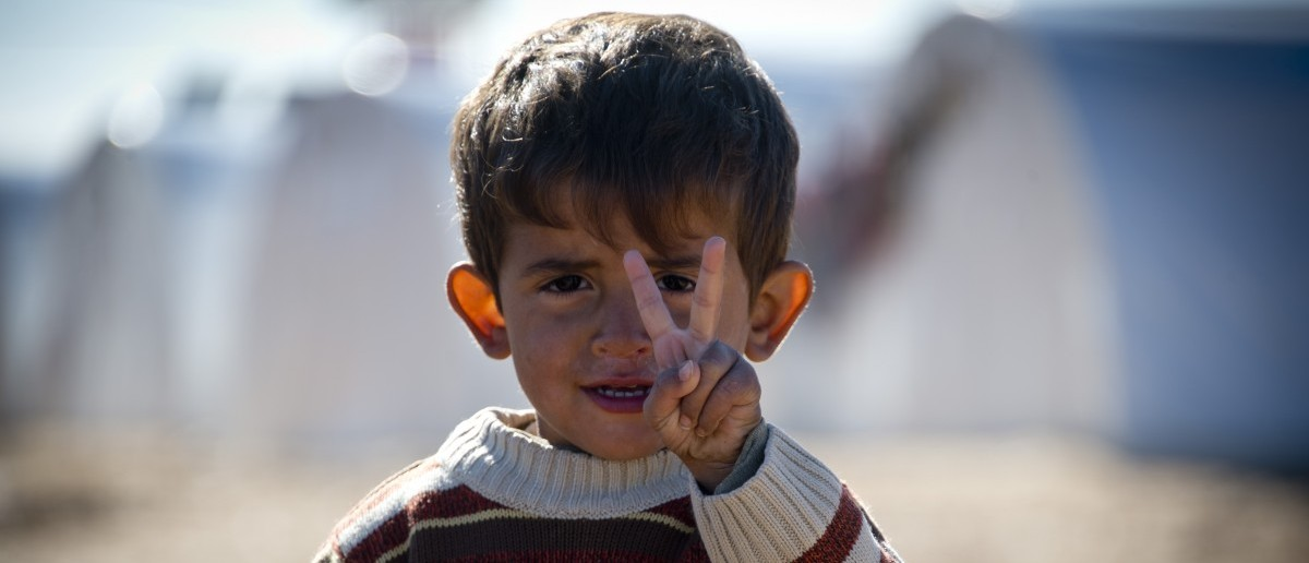 Standing in front of a row of plastic tents a young boy flashes the V-sign in a refugee camp on the border between Syria and Turkey near the northern city of Azaz on December 5, 2012. (ODD ANDERSEN/AFP/Getty Images)