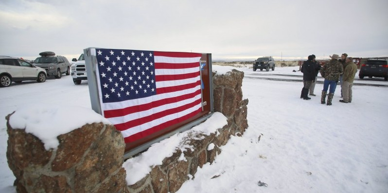 A U.S. flag covers a sign at the entrance of the Malheur National Wildlife Refuge near Burns, Oregon Jan. 3, 2016. (REUTERS/Jim Urquhart)