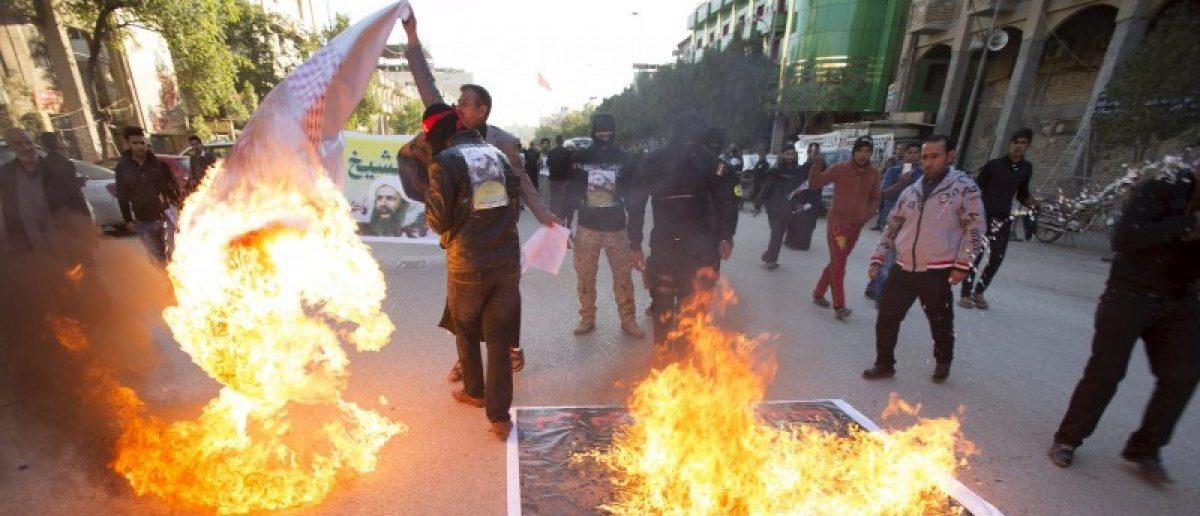 Supporters of Shi'ite cleric Moqtada al-Sadr burn posters of King Salman of Saudi Arabia against the execution of Shi'ite Muslim cleric Nimr al-Nimr in Saudi Arabia, during a demonstration in Kerbala January 4, 2016. REUTERS/Ahmed al-Husseini