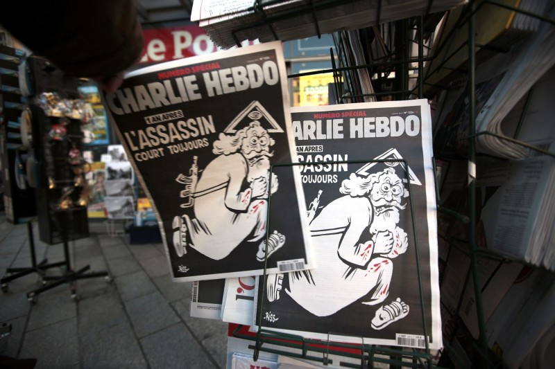 "A man takes a copy of the latest edition of French weekly newspaper Charlie Hebdo with the title ""One year on, The assassin still on the run"" displayed at a kiosk in Nice"