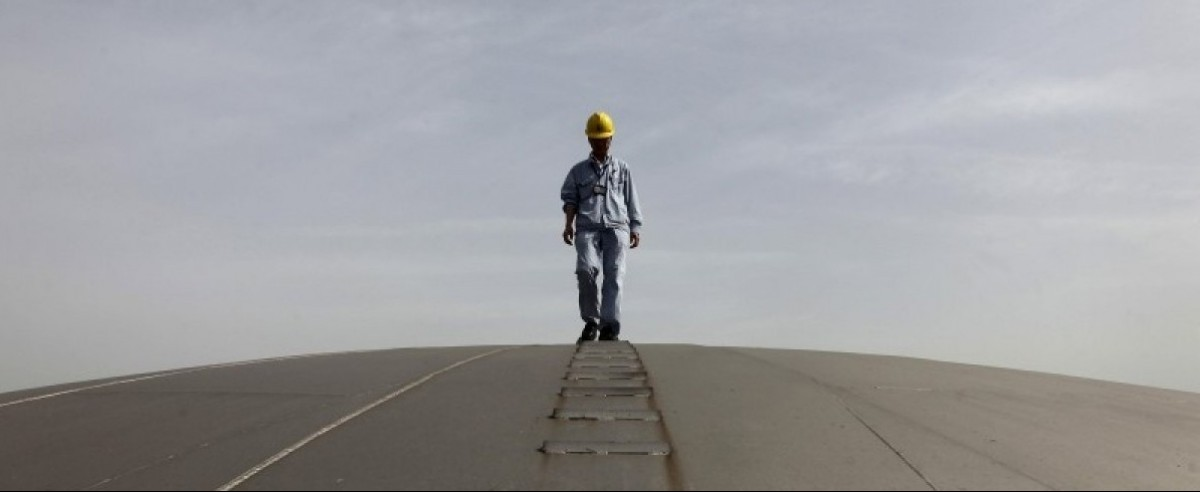 An employee walks on top of an oil tank at a Sinopec refinery in Wuhan, Hubei province, in this April 25, 2012 file picture.  REUTERS/Stringer/Files