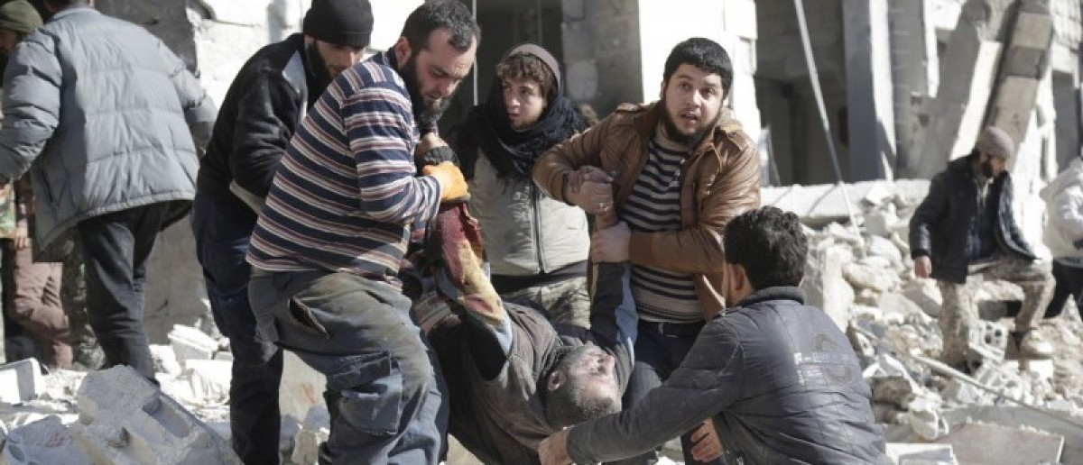 Residents carry an injured man in a site hit by what activists said were airstrikes carried out by the Russian air force in the rebel-controlled area of Maaret al-Numan town in Idlib province, Syria