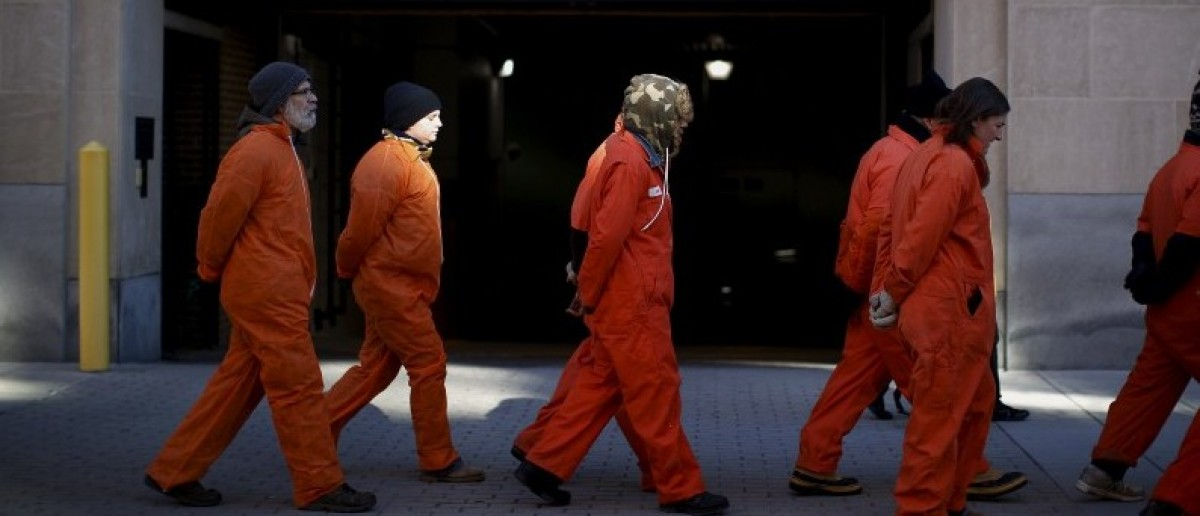 Human right activists dressed as prisoners of Guantanamo Bay march during a rally to demand the closure of Guantanamo prison, near the White House in Washington
