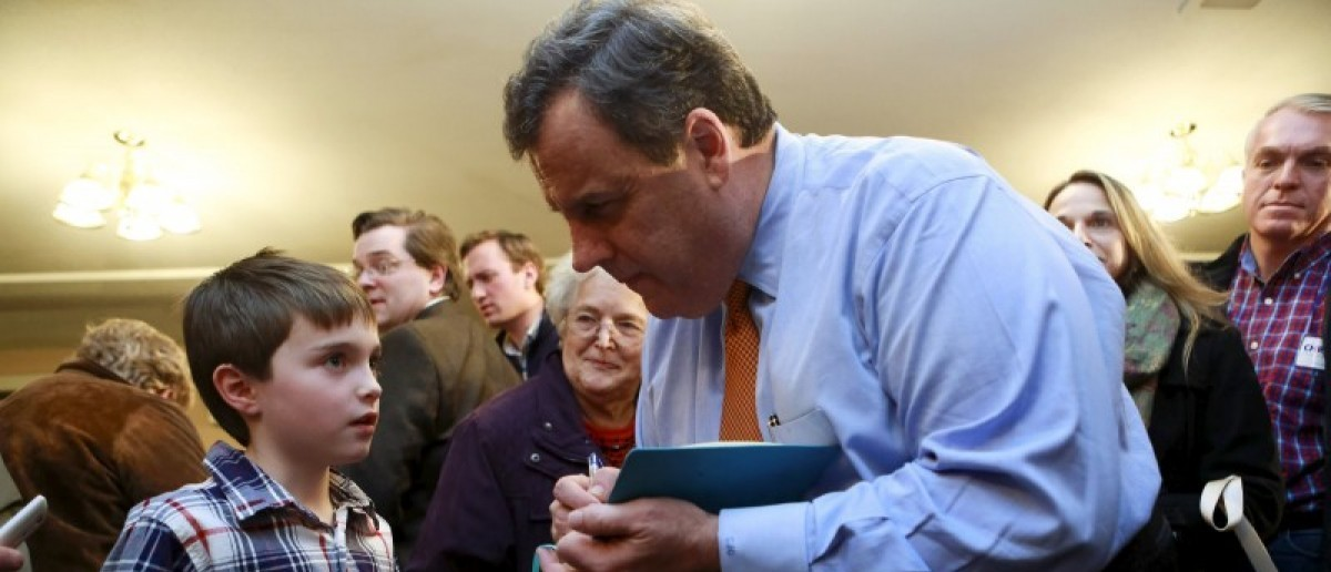 U.S. Republican presidential candidate and New Jersey Governor Chris Christie signs a notebook for Ethan Long, 8, of Nashua, New Hampshire, at a campaign town hall meeting in Merrimack, New Hampshire January 3, 2016. REUTERS/Katherine Taylor