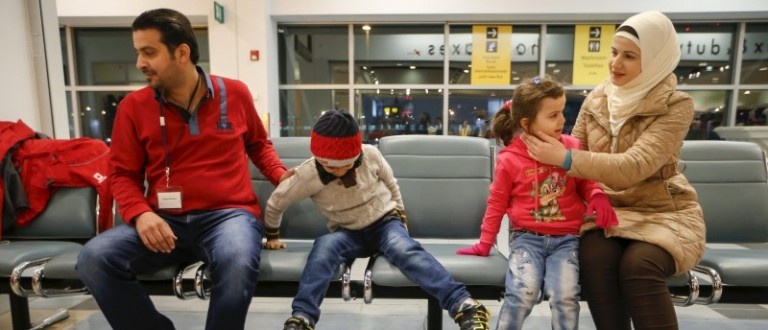 A Syrian refugee family sits down after arriving at the Pearson Toronto International Airport in Mississauga, Ontario, December 18, 2015. REUTERS/Mark Blinch