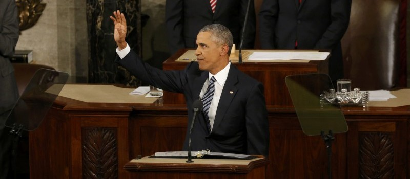 U.S. President Barack Obama waves as he arrives at the podium to deliver his State of the Union address to a joint session of Congress in Washington
