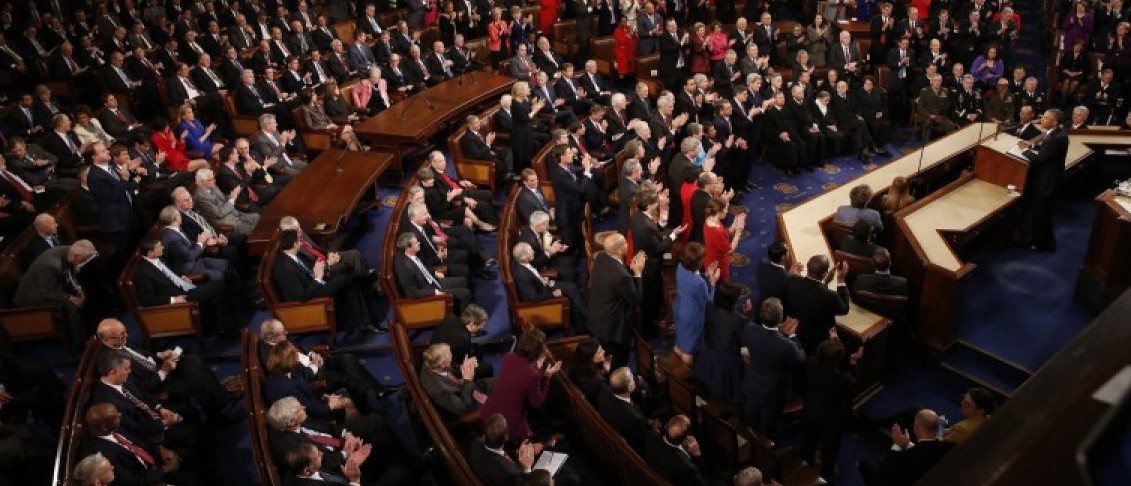 Democratic members of Congress rise to their feet for a standing ovation as Republican members remain seated during U.S. President Barack Obama's State of the Union address to a joint session of Congress in Washington, January 12, 2016. REUTERS/Jonathan Ernst