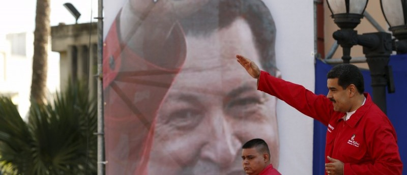 Venezuela's President Nicolas Maduro (R) gestures in front of a giant image of Venezuela's late President Hugo Chavez, during a meeting with workers of the Venezuelan state oil company PDVSA, outside Miraflores Palace in Caracas