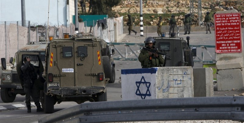 Israeli soldier stands guard near the scene where a Palestinian, who the Israeli military said tried to stab an Israeli soldier, was killed by Israeli troops, near Hebron