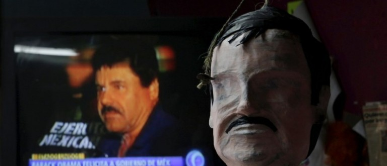 """A pinata in progress depicting the drug lord Joaquin """"El Chapo"""" Guzman is seen in front of a television showing a news bulletin of him at a workshop in Reynosa"""