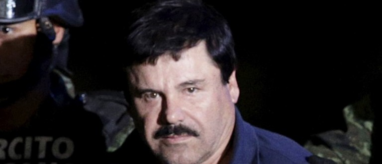 """Recaptured drug lord Joaquin """"El Chapo"""" Guzman is escorted by soldiers at the hangar belonging to the office of the Attorney General in Mexico City, Mexico in this January 8, 2016, file photo. REUTERS/Henry Romero/Files"""