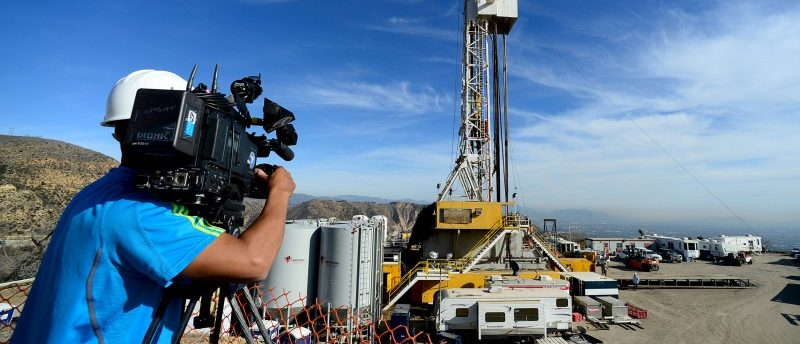 A TV cameraman works as crews from Southern California Gas Company and outside experts work on a relief well at the Aliso Canyon gas field above the Porter Ranch section of northwest Los Angeles, California in this December 9, 2015 pool photo. REUTERS/Dean Musgrove/Pool
