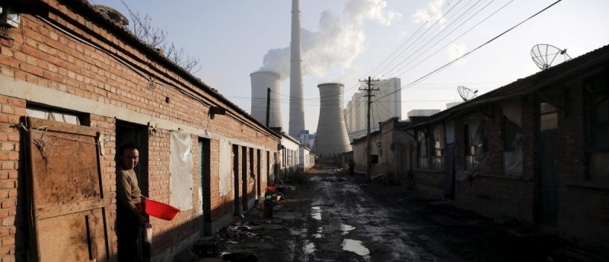 "A migrant worker steps out of his accommodation in an area next to a coal power plant in Beijing during a smog-free and also the last day of the city's first ""red alert"" for air pollution, in this December 10, 2015 file photo. REUTERS/Damir Sagolj/Files"