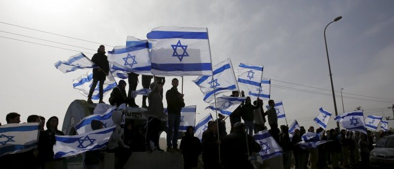 Israelis wave their national flag as a convey transporting the body of Dafna Meir, 38, passes on its way to a cemetery, near the West Bank Jewish settlement of Efrat January 18, 2016.  REUTERS/Ronen Zvulun