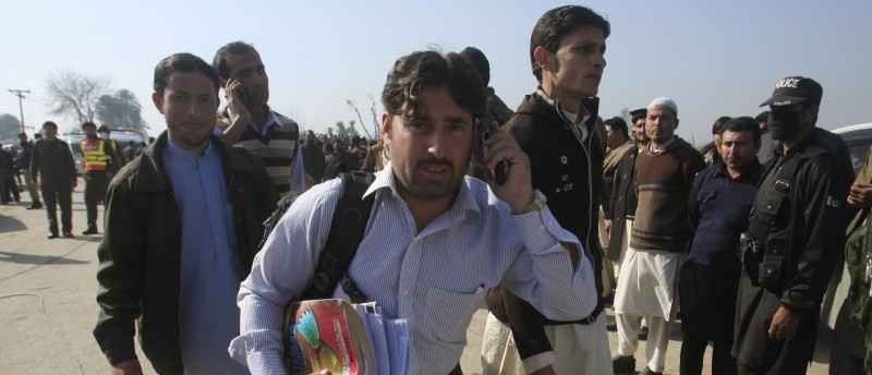 Student holding his books talks on a mobile phone, after he was rescued in a militant attack at Bacha Khan University in Charsadda