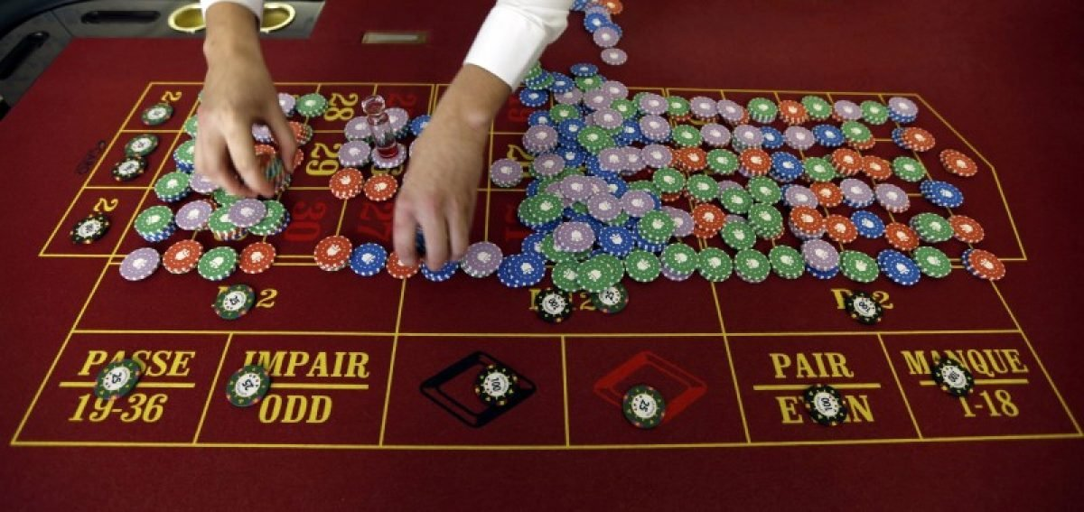 File photo of a young croupier trainee who practices near chips at a gaming table at the Cerus Casino Academy in Marseille