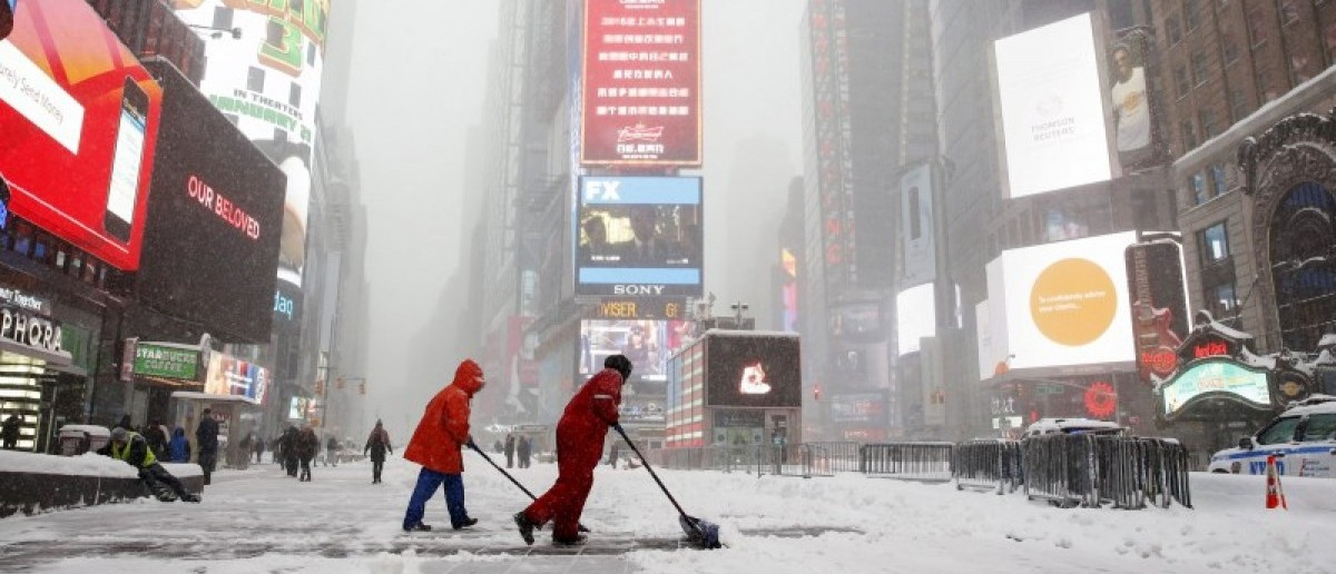 Workers shovel snow during a snowstorm at Times Square in the Manhattan borough of New York January 23, 2016. REUTERS/Shannon Stapleton