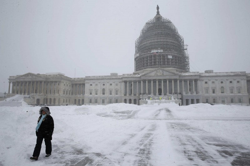 A person walks on the snow-covered grounds of the U.S. Capitol in Washington January 23, 2016. REUTERS/Jonathan Ernst