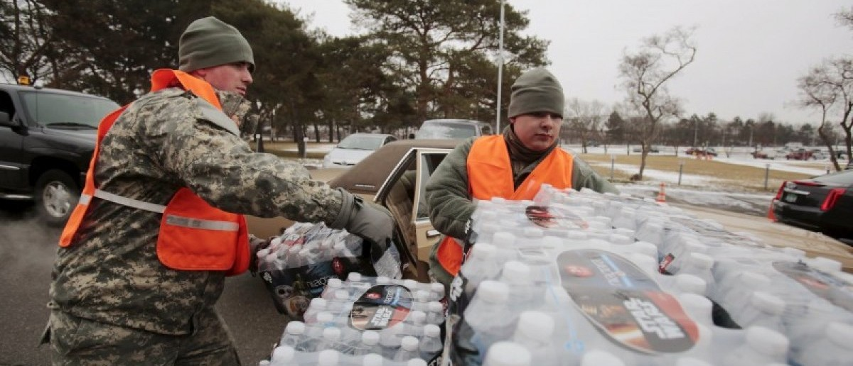 Michigan National Guard members help to distribute water to a line of residents in their cars in Flint, Michigan January 21, 2016. REUTERS/Rebecca Cook