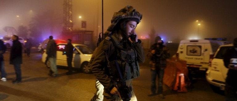 An Israeli soldier secures the area near the scene of what Israeli police said was a stabbing attack by two Palestinians on two Israelis in the West Bank Jewish settlement of Beit Horon