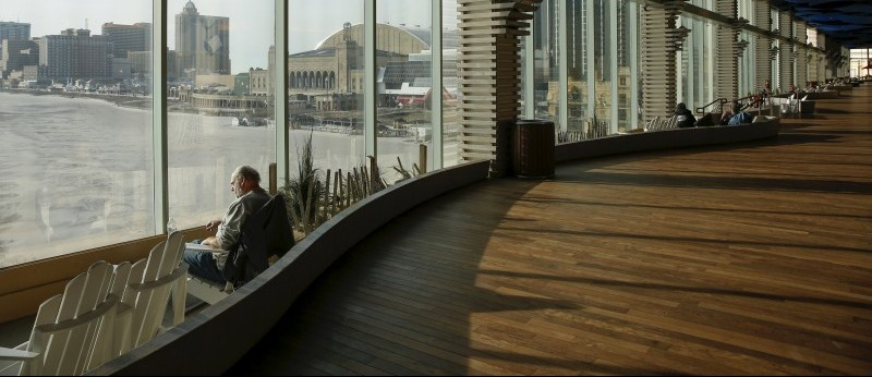 A man looks at the ocean through the windows of the Playground Pier in Atlantic City