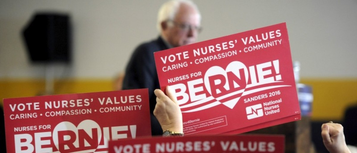 Supporters from the Nurses for Bernie Super PAC wave signs as U.S. Democratic presidential candidate Bernie Sanders speaks at a campaign event at United Steelworkers Local 310L in Des Moines, Iowa January 26, 2016. REUTERS/Mark Kauzlarich