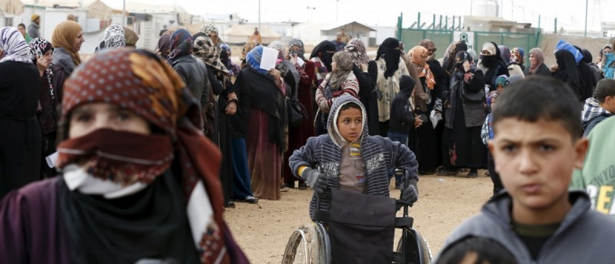 Syrian refugees stand in line as they wait for aid packages at Al Zaatari refugee camp in the Jordanian city of Mafraq, near the border with Syria, January 20, 2016. REUTERS/ Muhammad Hamed