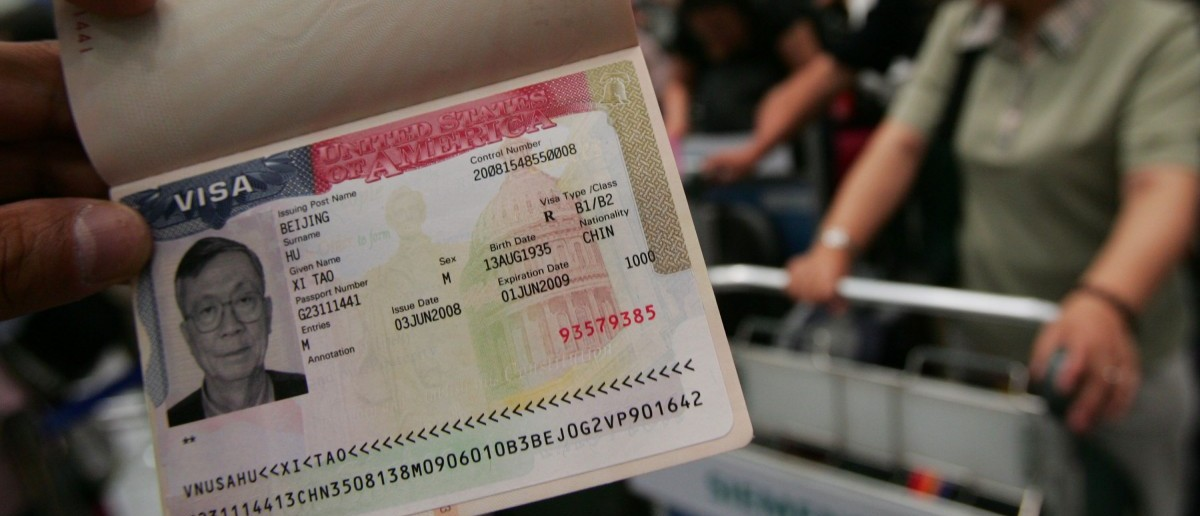 A U.S. visa is shown by a tourist as the first group of Chinese tourists set out to visit US at the Beijing Capital International Airport on June 17, 2008 in Beijing, China. (China Photos/Getty Images)