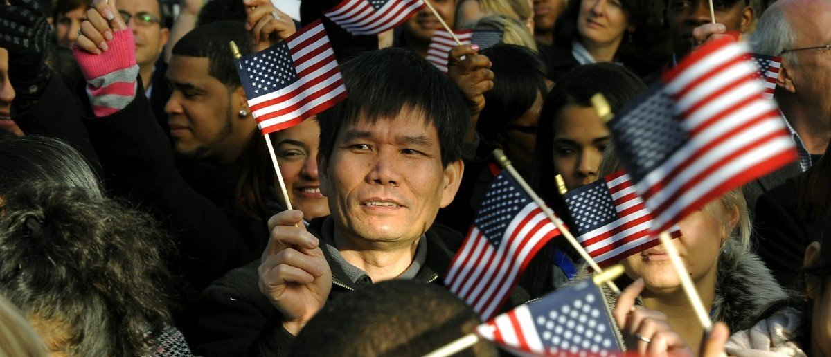 New citizens wave US flags before being sworn in during a Naturalization Ceremony conducted to swear in 125 new citizenship candidates at a ceremony on Liberty Island on October 28, 2011 to commemorate the 125th anniversary of the dedication of the Statue of Liberty. (TIMOTHY A. CLARY/AFP/Getty Images)