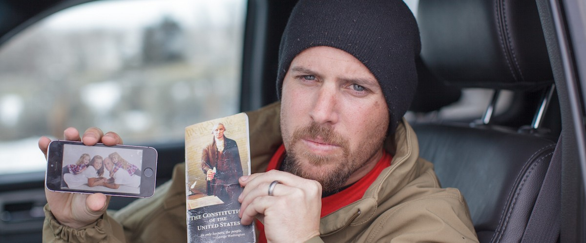 Jon Ritzheimer, 32, shows a family picture on his phone and a copy of the US Constitution to the media at the Malheur National Wildlife Refuge Headquarters near Burns, Oregon, January 4, 2016. The FBI on January 4 sought a peaceful end to the occupation by armed anti-government militia members at a US federal wildlife reserve in rural Oregon, as the standoff entered its third day. The loose-knit band of farmers, ranchers and survivalists -- whose action was sparked by the jailing of two ranchers for arson -- said they would not rule out violence if authorities stormed the site, although federal officials said they hope to avoid bloodshed. (ROB KERR/AFP/Getty Images)