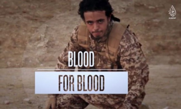 ISIS fighter and Paris attacker Abu Mujaed al-Baljiki just after being filmed beheading a prisoner. Screencapture: Heavy.com
