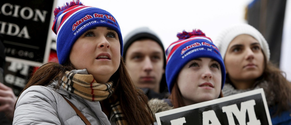 (L-R) Anti-abortion supporters Marian Rumley, Taylor Miller and Sophie Caticchio from Minnesota listen to speeches at the National March for Life rally in Washington January 22, 2016. The rally marks the 43rd anniversary of the U.S. Supreme Court's 1973 abortion ruling in Roe v. Wade. REUTERS/Gary Cameron
