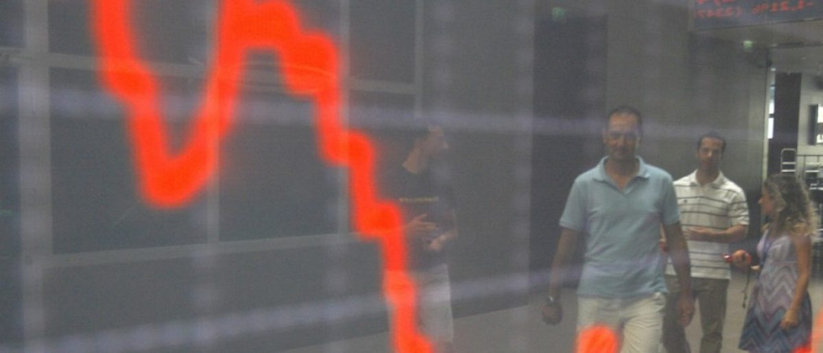 People are reflected at an index board inside the Athens stock exchange August 9, 2011. The global economy stumbled deeper into crisis as stock markets slumped further on Tuesday, with investors losing confidence that the United States and Europe can rein in their debt burdens quickly and avert a double-dip recession. REUTERS/Yiorgos Karahalis