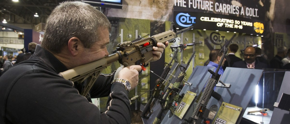 Mark Heitz of Tactical Firearms, looks over civilian version of Colt M4 carbine during SHOT Show in Las Vegas