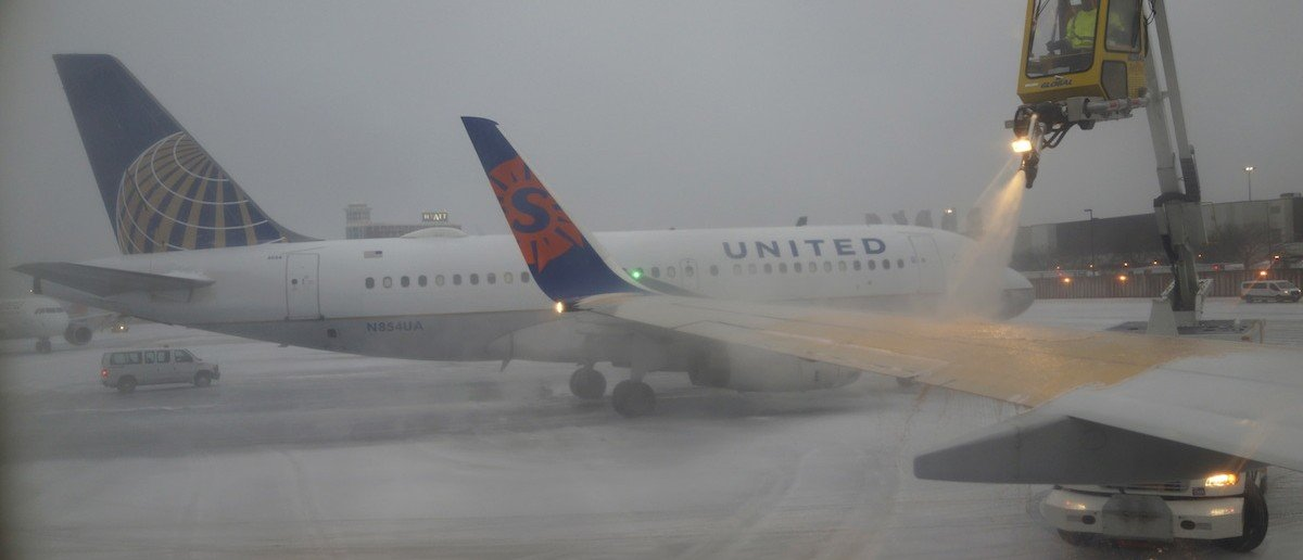 A Sun Country Airlines plane's wing is de-iced as a United Airlines plane waits at the de-icing station during a snowstorm at Logan International Airport in Boston, Dec. 29, 2015. (REUTERS/Lucy Nicholson)