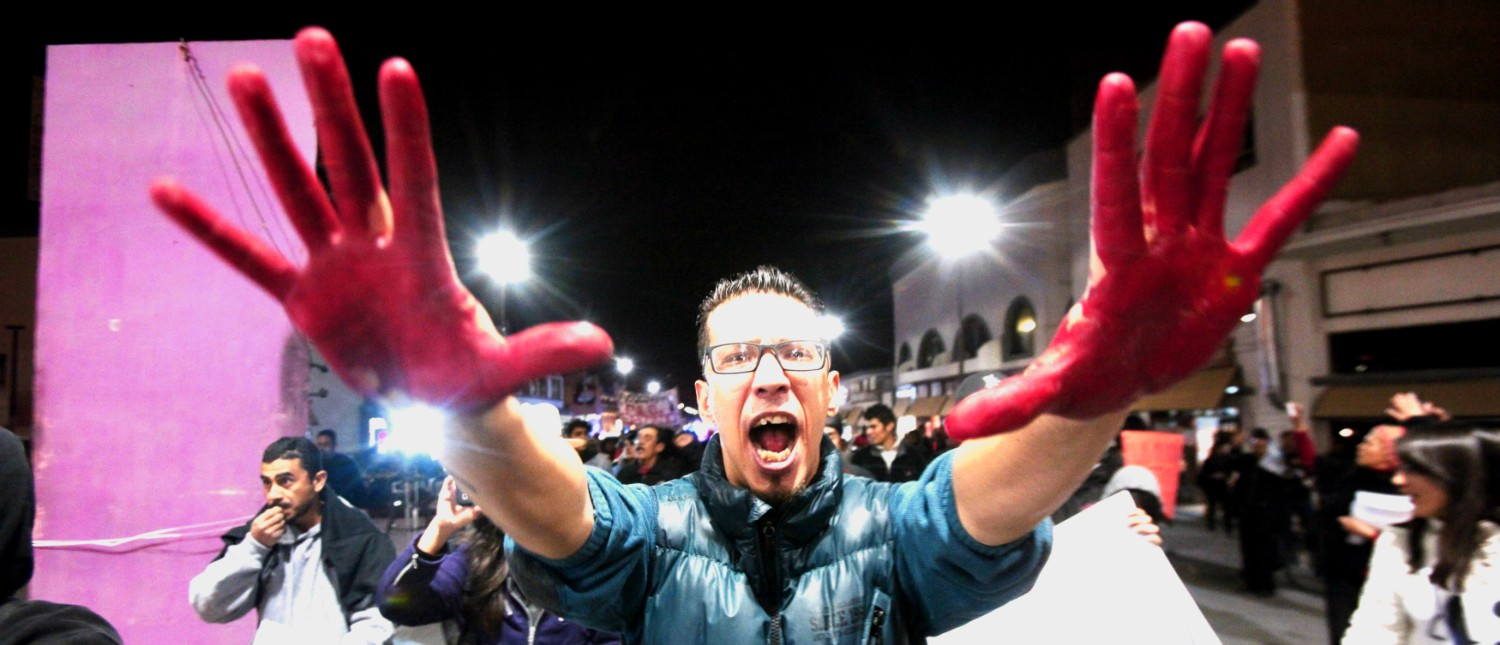 A demonstrator holds up his hands covered in red paint while yelling slogans in support of the 43 missing trainee teachers of the Ayotzinapa teachers' training college, during a protest at the International Santa Fe bridge and border crossing between Mexico and the U.S. in Ciudad Juarez January 26, 2015. The government says the students were abducted by corrupt police working for a local drug cartel, which it said incinerated their bodies at a nearby garbage dump. REUTERS/Jose Luis Gonzalez