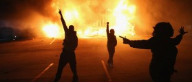 Demonstrators celebrate as a business burns after it was set on fire during rioting following the grand jury announcement in the Michael Brown case on November 24, 2014 in Ferguson, Missouri. Ferguson has been struggling to return to normal after Brown, an 18-year-old black man, was killed by Darren Wilson, a white Ferguson police officer, on August 9. His death has sparked months of sometimes violent protests in Ferguson. A grand jury today declined to indict officer Wilson. (Scott Olson/Getty Images)