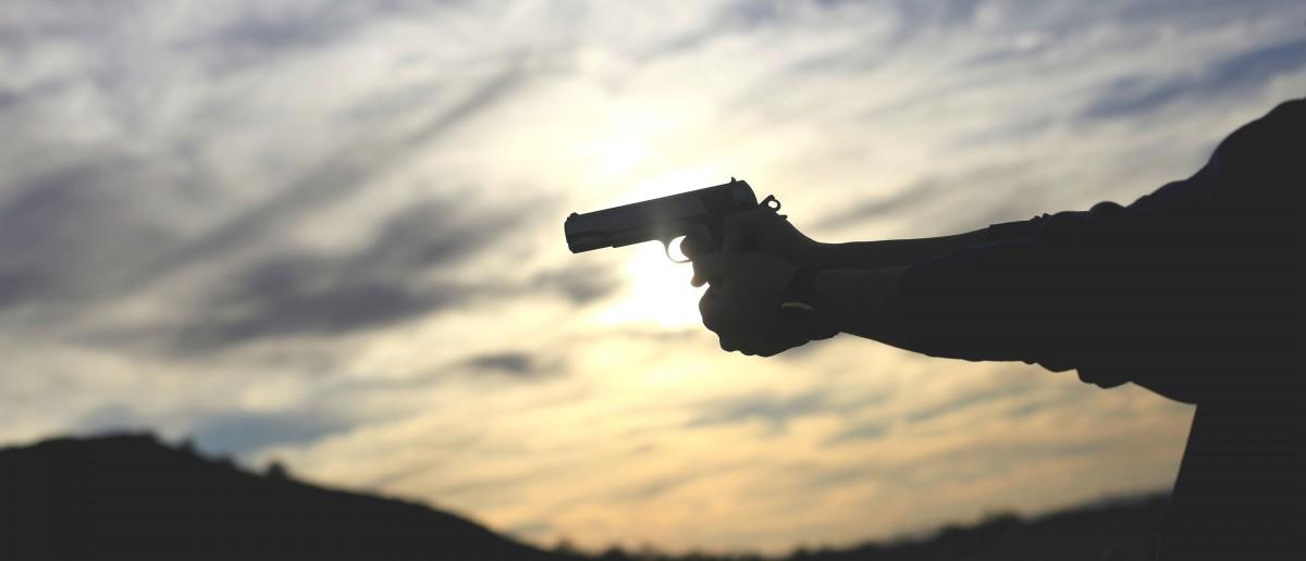 A man fires his handgun along a mountain range in Buckeye, Arizona January 20, 2013. REUTERS/Joshua Lott