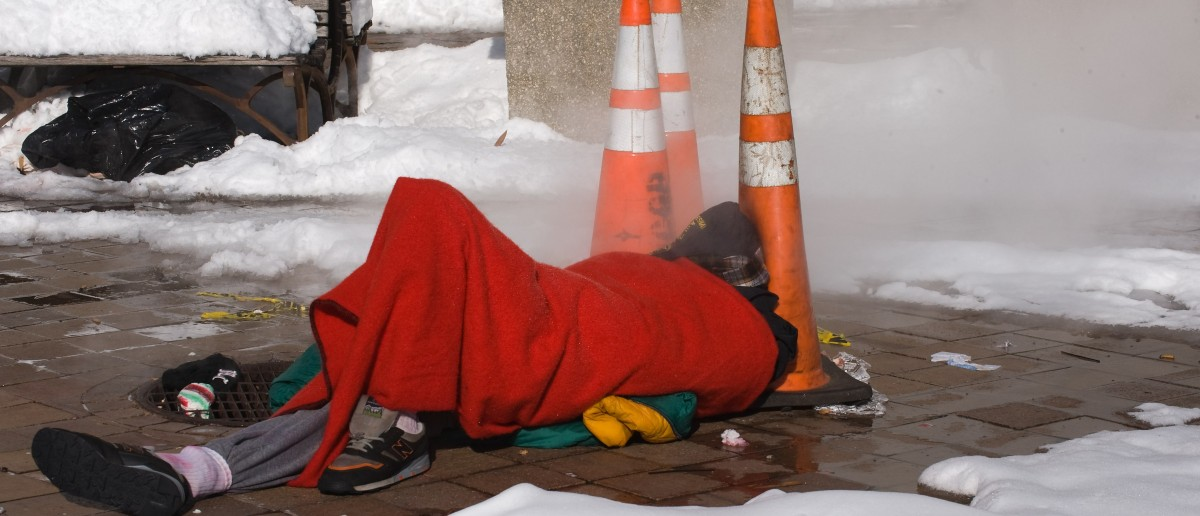 A homeless man sleeps next to a steaming manhole on Pennsylvania Avenue in Washington on December 20, 2009. A ferocious snow storm blanketed much of the eastern United States, cutting power to hundreds of thousands of homes, paralyzing air traffic and stranding motorists. The governors of Virginia, Maryland, West Virginia and Delaware declared states of emergency in advance of the storm, the worst to hit the region in decades. AFP PHOTO/Nicholas KAMM (Photo credit should read NICHOLAS KAMM/AFP/Getty Images)