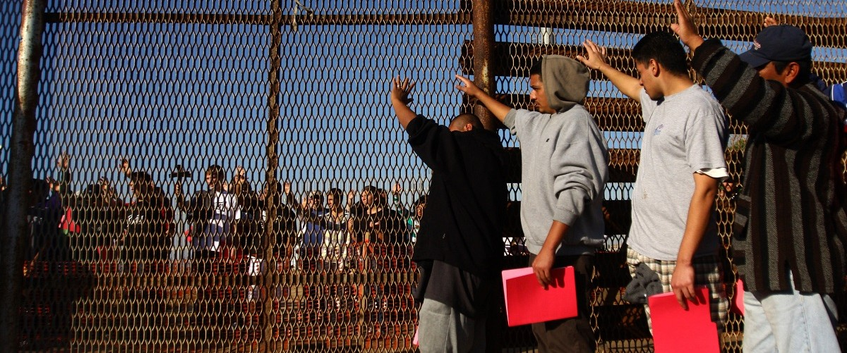 A group of recently deported immigrants stand near the double steel fence that separates San Diego and Tijuana at the border in Tijuana
