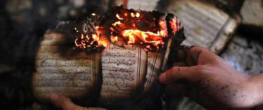 A Palestinian man displays a copy of Islam's holy book, the Koran, still burning inside a mosque that was set ablaze by Israeli settlers in al-Mughayir, in the occupied West Bank near the Jewish settlement of Shilo, on November 12, 2014. Israeli settlers torched the West Bank mosque in an apparent revenge attack, after separate Palestinian knife attacks the previous day killed a settler in the southern Western Bank and an Israeli soldier in Tel Aviv. Abbas Momani/AFP/Getty Images.