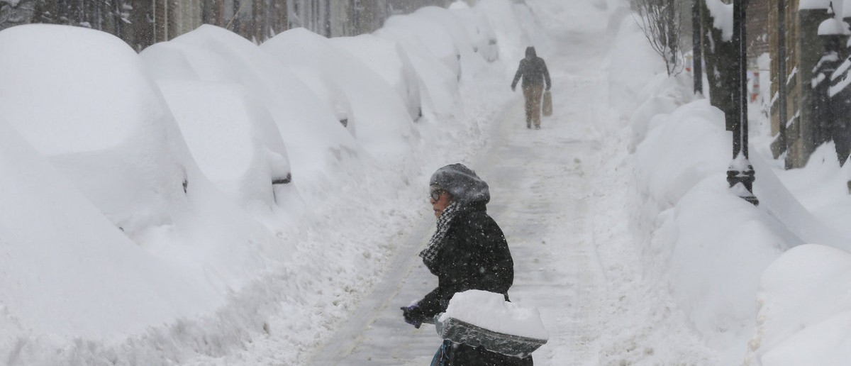A woman shovels snow on Joy Street during a winter blizzard in Boston, Massachusetts February 15, 2015. The U.S. Northeast faced yet another major winter storm at the weekend, with blizzard conditions in six states' coastal regions, much of which is already buried under record-setting snow, forecasters said. In Boston, snow fell hard Saturday afternoon, pausing for an evening lull before picking up again. Forecasters predicted accumulations of up to 14 inches (36 cm) of snow through Sunday. REUTERS/Brian Snyder (UNITED STATES - Tags: ENVIRONMENT)