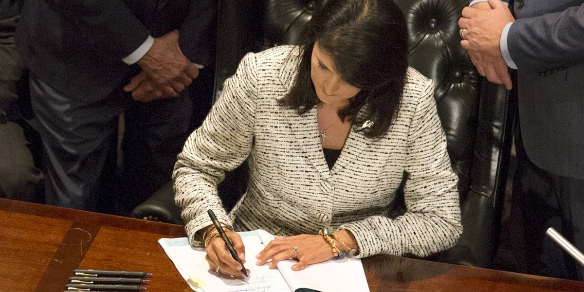 South Carolina Governor Nikki Haley signs legislation permanently removing the Confederate battle flag from the state capitol grounds, following an emotional debate spurred by the massacre of nine black churchgoers last month, on Thursday in Columbia, South Carolina July 9, 2015. REUTERS/Jason Miczek
