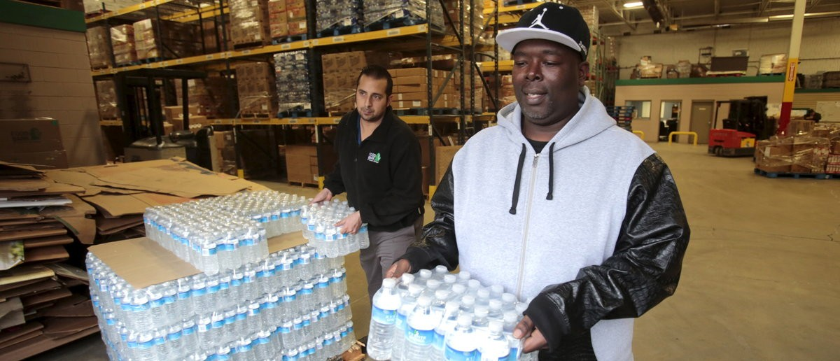 Anthony Fordham picks up water at the Food Bank of Eastern Michigan to deliver to a school after elevated levels of lead were found in the city's water in Flint, Michigan December 16 2015 REUTTERS/Rebecca Cook
