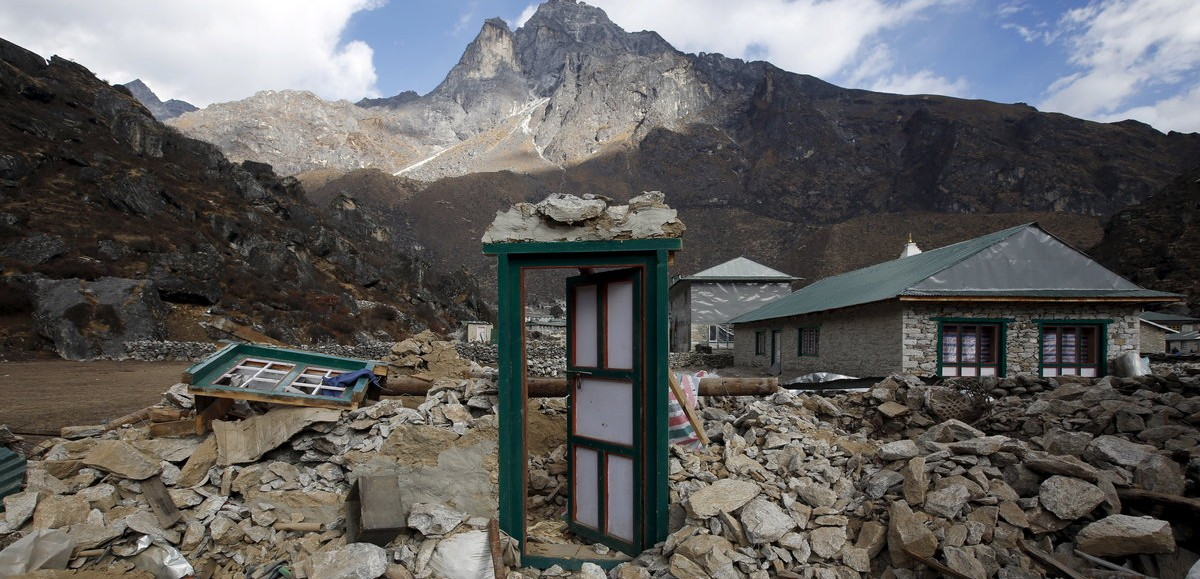 A door of a collapsed house stands after the earthquake damaged it earlier this year at Khumjung, a typical Sherpa village in Solukhumbu district also known as the Everest region, in this picture taken November 30, 2015. To match Insight QUAKE-NEPAL/SHERPAS REUTERS/Navesh Chitrakar