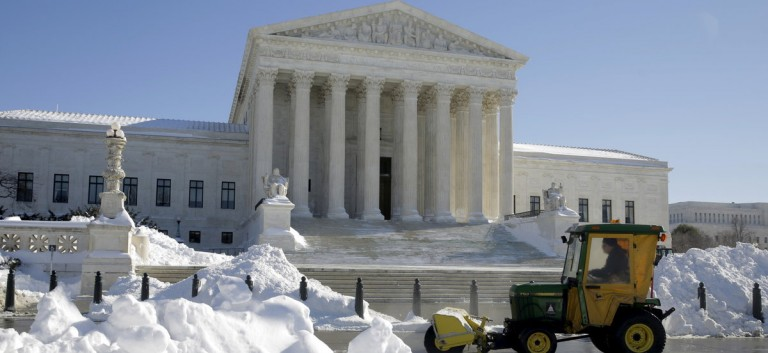 A man uses a sweeper to clear snow from in front of the Supreme Court after a major winter storm swept over Washington January 24, 2016. The National Weather Service said 17.8 inches (45.2 cm) fell in Washington, tying as the fourth-largest snowfall in the city's history. REUTERS/Joshua Roberts