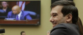 """Martin Shkreli, former CEO of Turing Pharmaceuticals LLC, smiles as he listens to House Oversight and Government Reform Committee ranking member Rep. Elijah Cummings (seen on video screen) during a hearing on """"Developments in the Prescription Drug Market Oversight"""" on Capitol Hill in Washington February 4, 2016. (REUTERS/Joshua Roberts)"""