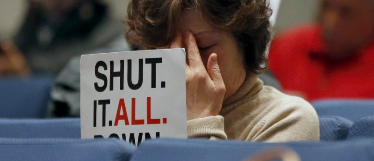 A woman presses her forehead as she sits with a group of Porter Ranch residents holding protest signs at a meeting of air quality regulators to discuss potential rules against the utility that operates the site of a gas leak in Porter Ranch, in Diamond Bar, California, United States, January 20, 2016. REUTERS/Lucy Nicholson