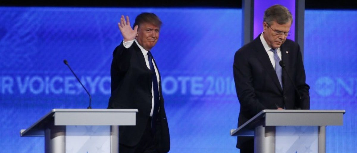 Republican presidential candidate and businessman Donald Trump (L) walks past former Governor Jeb Bush (R) as he takes the stage to participate in the Republican U.S. presidential candidates debate sponsored by ABC News at Saint Anselm College in Manchester, New Hampshire February 6, 2016. REUTERS/Carlo Allegri