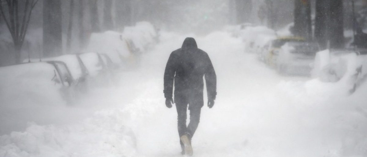 A man walks along a street covered by snow during a winter storm in Washington, January 23, 2016. REUTERS/Carlos Barria